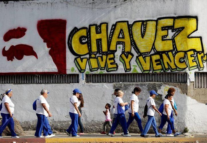 """Peatones caminan junto a una barda pintada que dice """"Chávez vive y prevalecerá"""", fuera del hospital militar en Caracas. (Agencias)"""