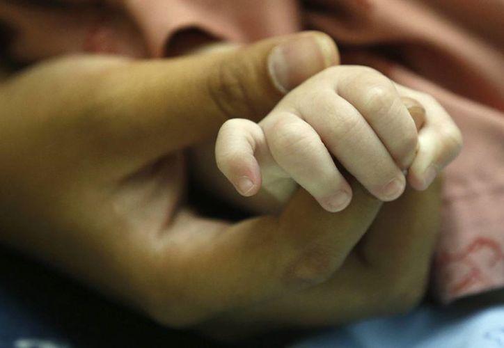 Pattharaomon Janbua, de 21 años, sostiene la manita de su hijo biológico con síndrome de Down Gammy, de siete meses, en un hospital de la provincia de Chonburi, Tailandia. (EFE)