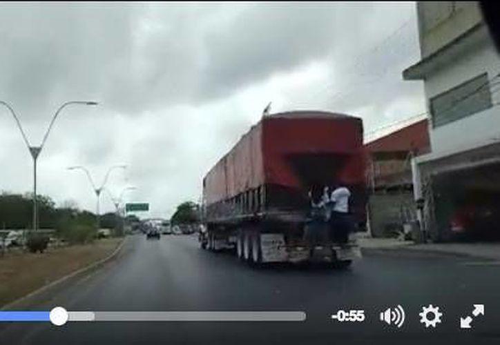 Un par de jóvenes viajan colgados de un tráiler sobre la avenida López Portillo. (Redacción/SIPSE)