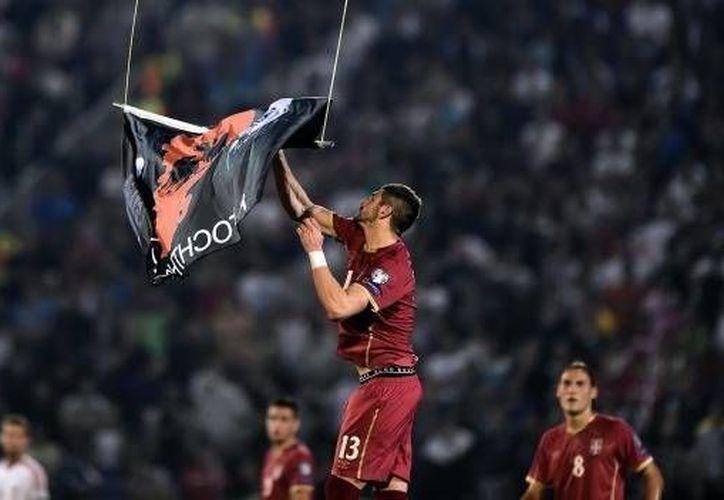 Jugadores de Albania y Serbia se enfrentaron debido a una bandera albana que sobrevoló en partido eliminatorio europeo. (mexico.cnn.com)