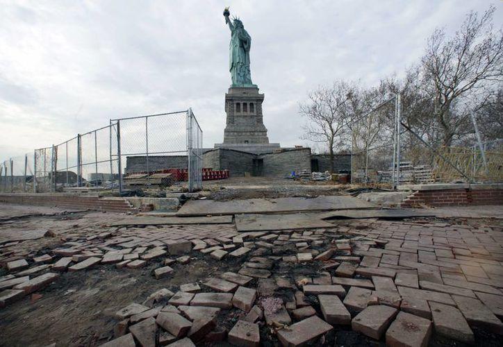 En esta fotografía de archivo de noviembre de 2012, se observa a la Estatua de la Libertad sobre partes de un camino dañado por la tormenta Sandy. La famosa efigie está en riesgo de desaparecer con el aumento del nivel del mar. (Foto AP/Richard Drew, Archivo)