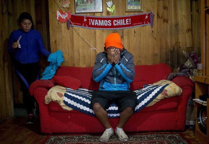 El buceador José Luis Cifuentes se cubre la cara exhausto y frustrado mientras dice que no tiene dinero para comprar comida, en la casa de su suegra en Ancud. (Agencias)