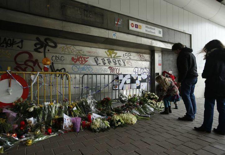 Gente coloca ofrendas florales en la entrada de la estación del metro Maelbeek, escenario de uno de los ataques en Brusela. (Agencias)