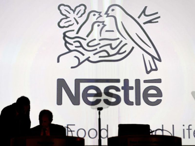 Nestle's directors speak in front of the Nestle's logo during the general meeting of Nestle Group, in Lausanne, Switzerland. (AP)
