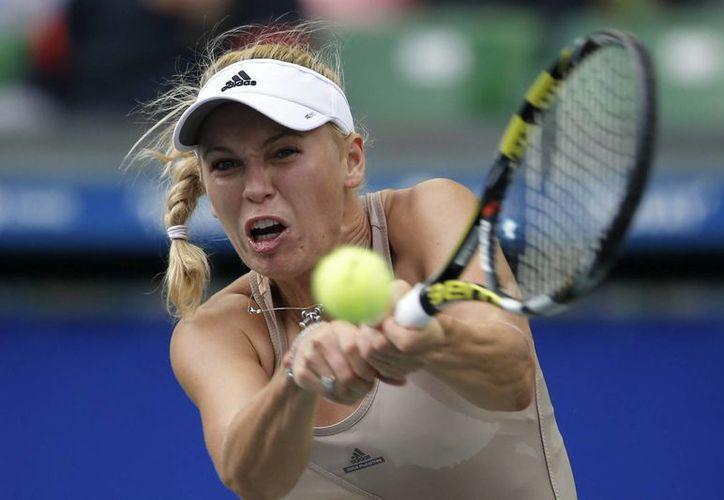 La tenista danesa Caroline Wozniacki devuelve la bola a la española Carla Suárez Navarro durante el partido que enfrentó a ambas en el torneo de Tokio. (EFE)