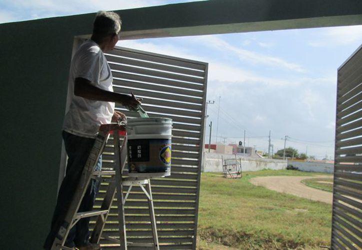 Un hombre trabaja en los últimos detalles del Centro Regional de Alto Rendimiento de Progreso. (Manuel Pool/SIPSE)