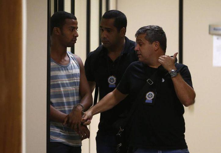Policías brasileños escoltan a Raí de Souza (i) en Río de Janeiro. Raí, de 22 años, es sospecho de participar en la violación de una adolescente de 16 años. (EFE/Archivo)