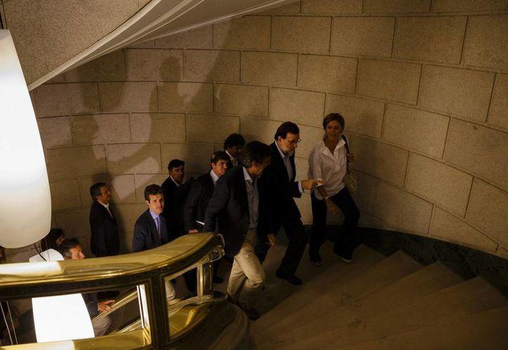 El presidente interino del gobierno de España Mariano Rajoy (segundo desde la derecha), sube unas escaleras después de ofrecer una conferencia de prensa sobre su reunión con el líder del partido Ciudadanos Albert Rivera en el Parlamento español en Madrid. (AP/Daniel Ochoa de Olza)