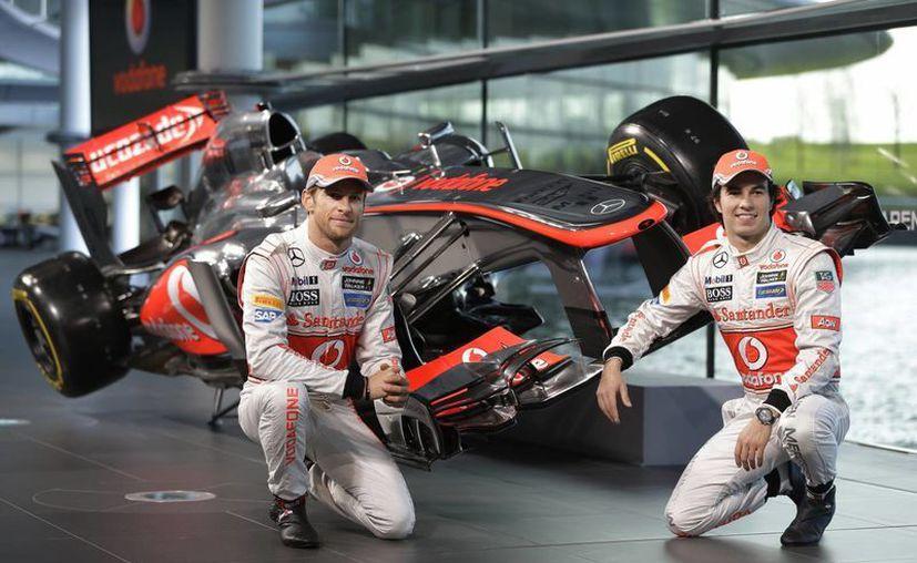 Button y el 'Checo' Pérez (d) posan con el nuevo modelo que utilizarán en este año. (AP)