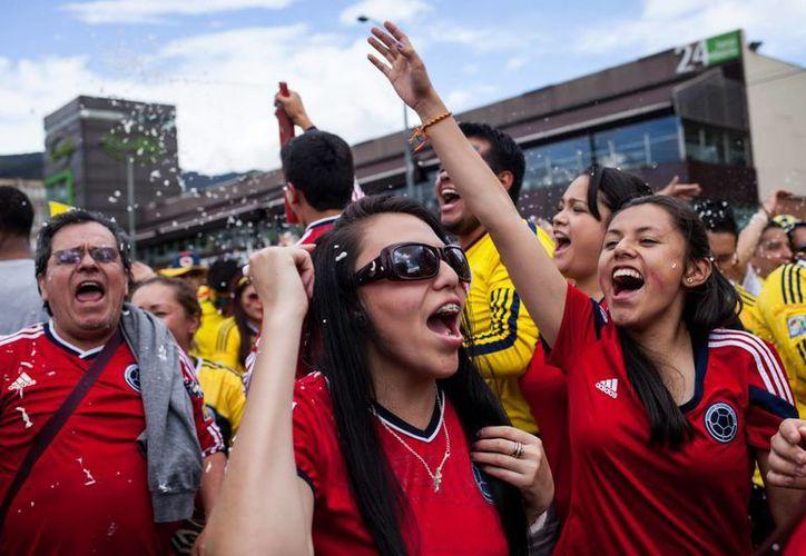 Aficionados de Colombia celebran en Bogotá el pase a cuartos de final en el Mundial. (EFE)