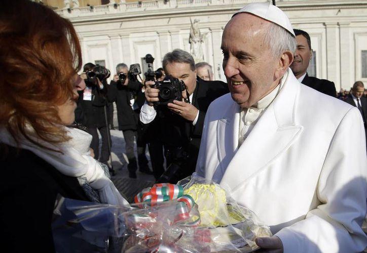 La periodista mexicana Valentina Alazraki al momento de entregarle al Papa Francisco un pastel en forma de sombrero de charro con motivo de su cumpleaños. (Agencias)