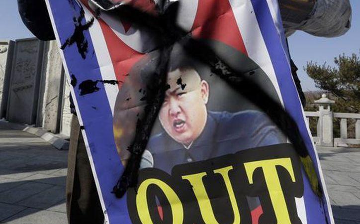 Un activista de Corea del Sur muestra un retrato desfigurado del líder norcoreano, Kim Jong Un. (Agencias)
