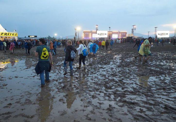 Asistentes al festival 'Rock am Ring' en Alemania caminan sobre el barro tras el paso de una tormenta eléctrica que dejó 71 heridos. (EFE)