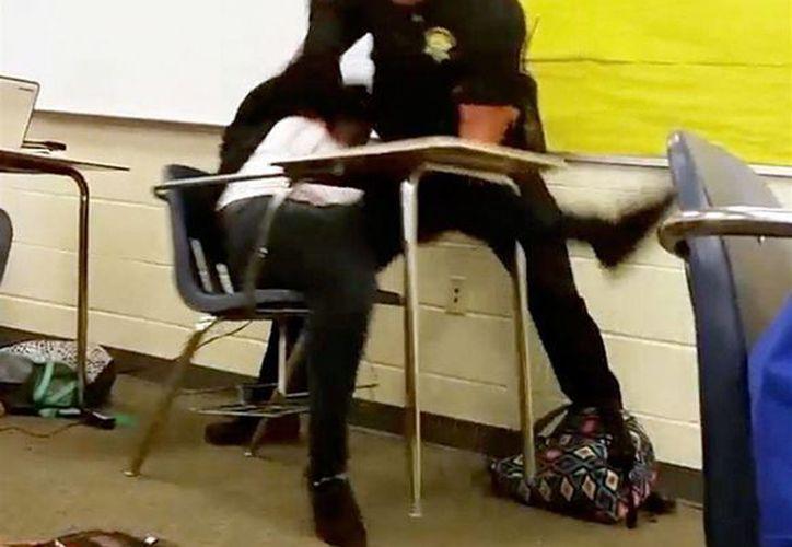 Imagen tomada de un video captado por un estudiante de la secundaria Spring Valley, el agente Ben Fields intenta retirar a la fuerza a una estudiante que se rehusó a salir de su clase de matemáticas en Columbia, South Carolina. (Foto AP)