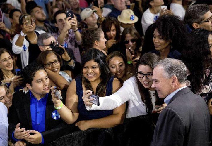 Tim Kaine se toma una selfie con una  seguidora en la Arena de la Universidad Internacional de Florida; el candidato demócrata a la Vicepresidencia de Estados Unidos hizo énfasis en su apoyo a la comunidad latina. (AP)