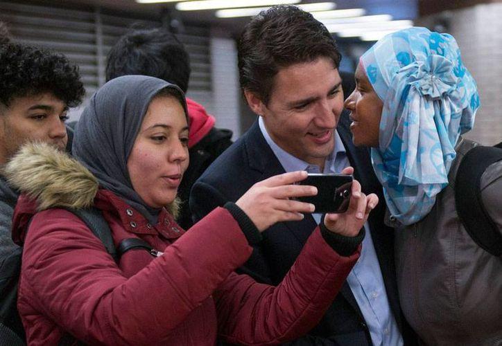 El nuevo primer ministro de Canadá, Justin Trudeau, accede a tomarse fotos con sus seguidores. El político es hijo de Pierre Tredeau, quien también ocupara el máximo cargo del Gobierno de Canadá. (AP)
