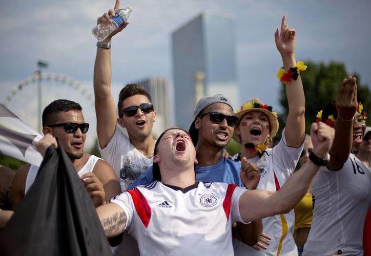 Lucke Ehret (c), de Mannheim, Alemania, celebra en Atlanta, EU, con sus amigos la obtención del título de Alemania como campeón del mundo en Brasil.(Foto: AP)