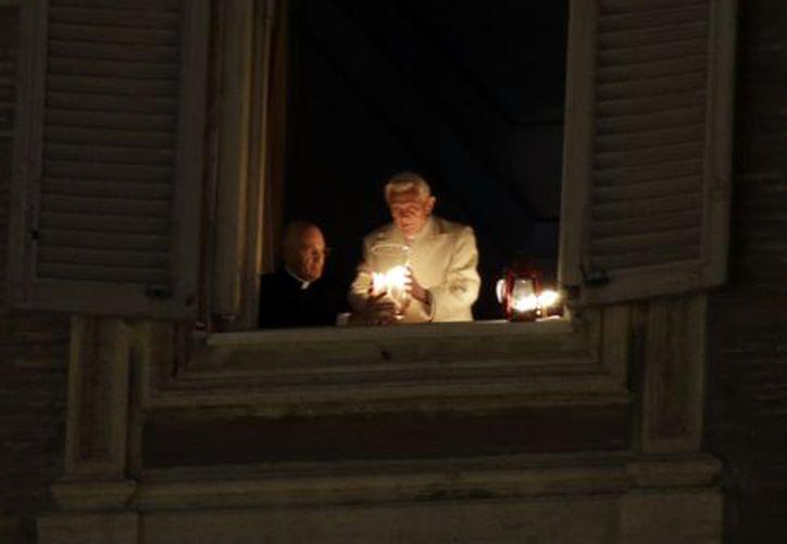 El Papa Benedicto XVI al momento de colocar la vela. (Agencias)
