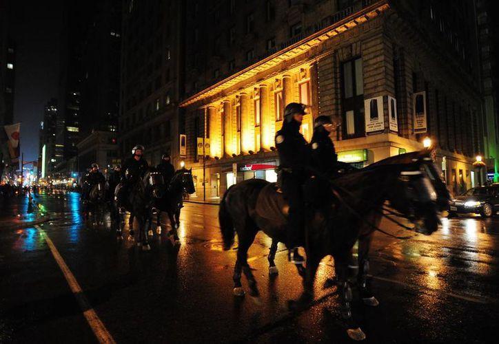 En la imagen, integrantes de la Policía Montada hacen guardia en una calle de Toronto, Canadá. (EFE)
