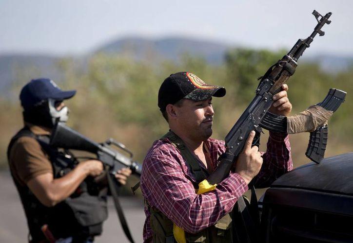 Hombres armados que integran las autodefensas de Michoacán controlan la entrada a Antúnez. (Agencias)