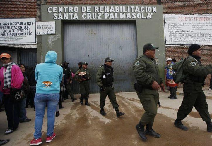Oficiales de policía caminan afuera de la cárcel de Palmasola mientras familiares esperan noticias de sus seres queridos detenidos en Santa Cruz, Bolivia. (Agencias)
