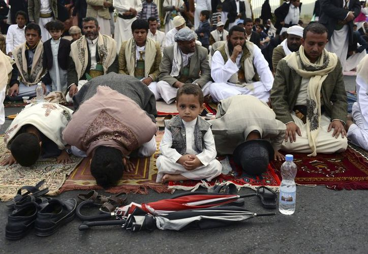 Chico de Yemen se sienta con su familia mientras rezan en Sanaa, Yemen. (Agencias)