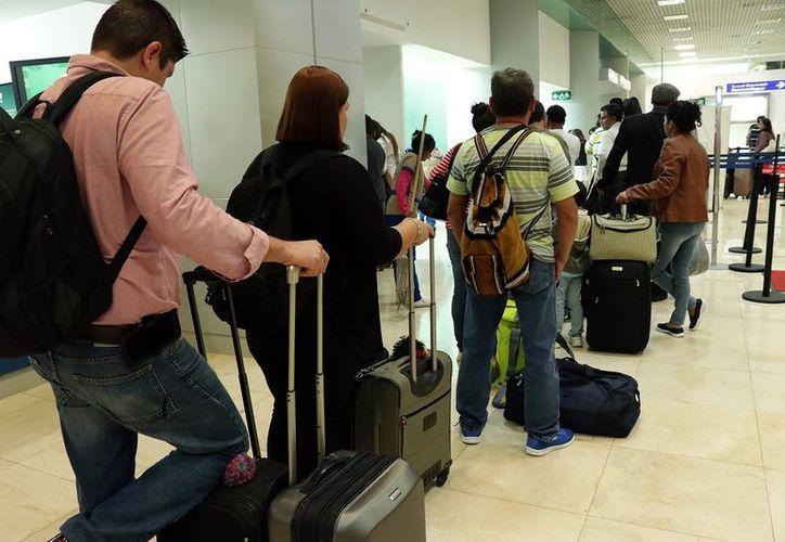 Largas filas de viajeros se registraron ayer en el aeropuerto de Mérida. (Foto: Milenio Novedades)