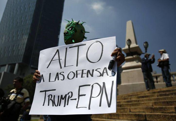 Un puñado de manifestantes llevan carteles con mensajes como 'Trump no eres bienvenido' y 'Fuera Trump, fuera EPN' y 'Alto a las ofensas de Trump y EPN', en referencia al presidente de México, Enrique Peña Nieto, ya que se reunieron ambos este día, en la Ciudad de México. (Foto AP/Rebecca Blackwell)
