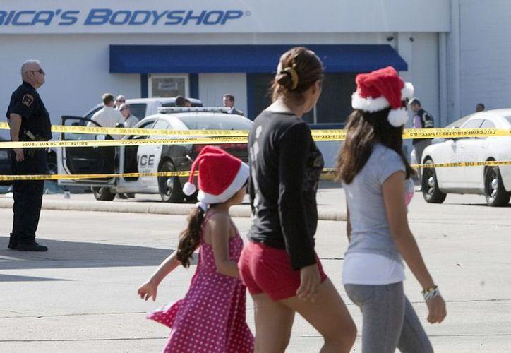 Sarai Rojas (c) y sus hijas caminan frente a al escena del crimen en Houston. (Agencias)