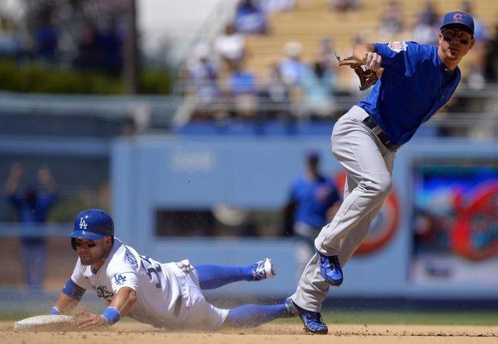 El angelino Skip Schumaker (i) se barre en segunda base mientras el cachorro Darwin Barney trata de hacer un out en primera. (Agencias)