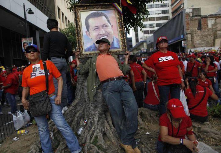 Un venezolano sostiene un retrato de Hugo Chávez. (Agencias)