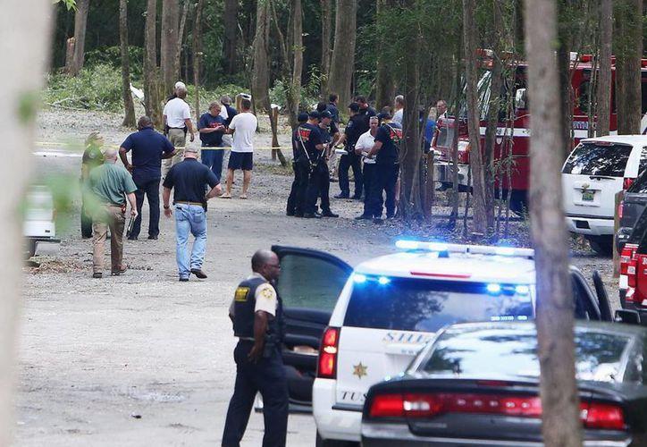 Autoridades trabajan en el sitio donde cayó un avión pequeño cerca del Aeropuerto Regional Tuscaloosa, en Northport, Alabama este domingo 14 de agosto de 2016. (Erin Nelson/The Tuscaloosa News vía AP)