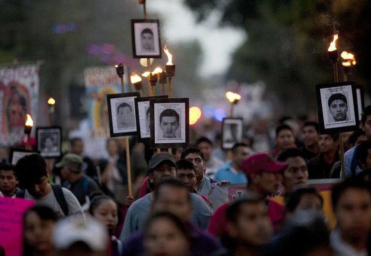 Parientes de los 43 estudiantes desaparecidos de la escuela normal Isidro Burgos de Ayotzinapa, Guerrero, marchan por la ciudad de México con fotos de las víctimas. (Agencias)