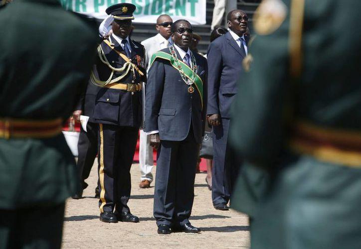 El reelecto presidente de Zimbabue, Robert Mugabe (c) inspecciona la guardia de honor a su llegada para conmemorar el Día de los Héroes en Harare, Zimbabue. (EFE)