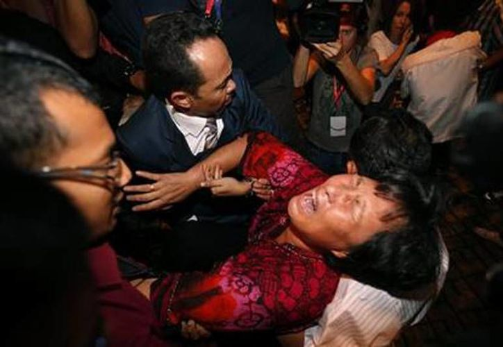 Una mujer china es retirada del salón donde se dio una conferencia de prensa para informar los resultados de la búsqueda de la aeronave. (Agencias)