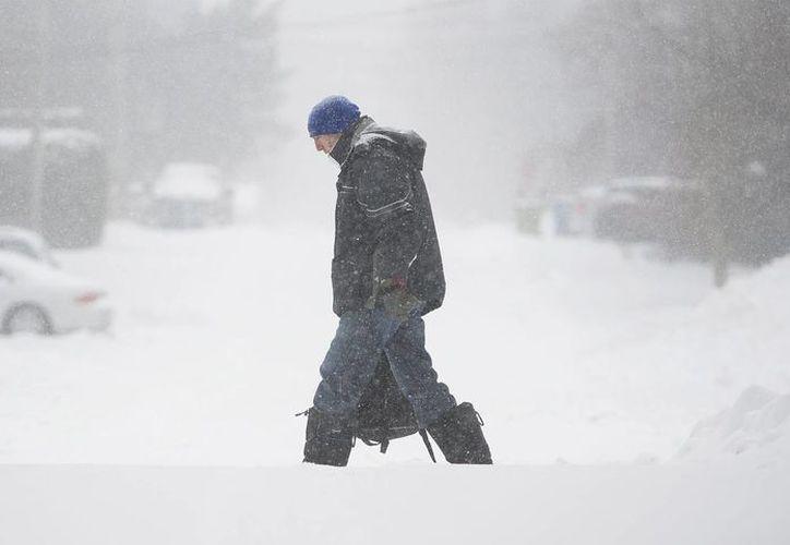 Imagen de un hombre que camina por una calle llena de nieve. Esta es la primera tormenta invernal importante del norteamérica. (Graham Hughes / The Canadian Press via AP)