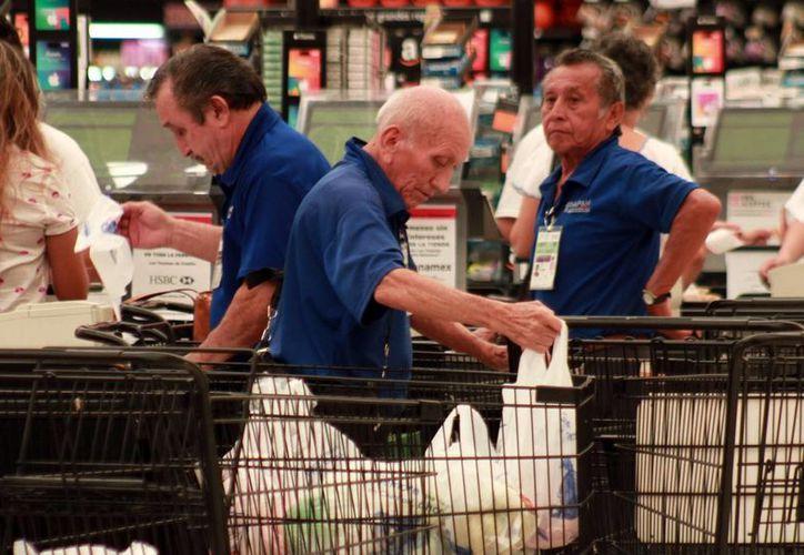 La STPS sugiere ahorrar entre 10 y 20 por ciento del aguinaldo en el fondo de ahorro para el retiro. Imagen de un grupo de adultos de la tercera edad que trabaja en el supermercado. (Milenio Novedades)