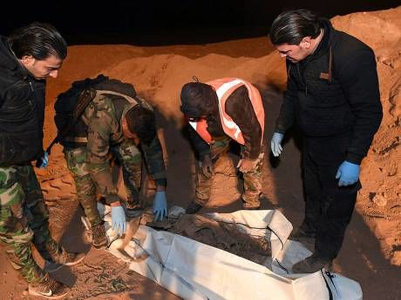 Syrian security forcé members check human remains  at the site of two graves, near the northern city of Raqqa, Syria.