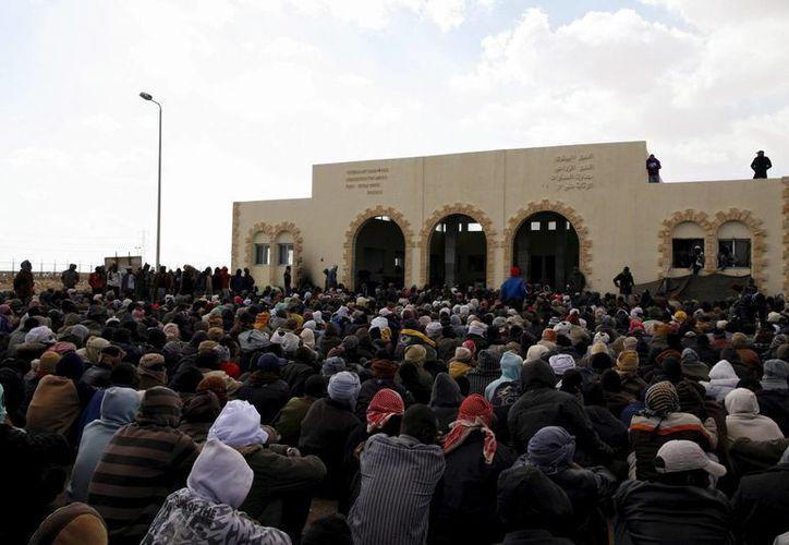 Al menos 11 personas fallecieron al naufragar un barco con migrantes en Egipto. En la foto, de archivo, unos refugiados sin papeles escuchan una declaración en el exterior del edificio de inmigración situado en el puesto fronterizo de Al Salum, Egipto. (EFE/Archivo)