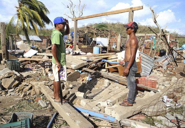 Dos hombres observan el estado en que se encuentran unas casas en la comunidad de Melaque, Jalisco, tras el paso del huracán 'Patricia'. (EFE)