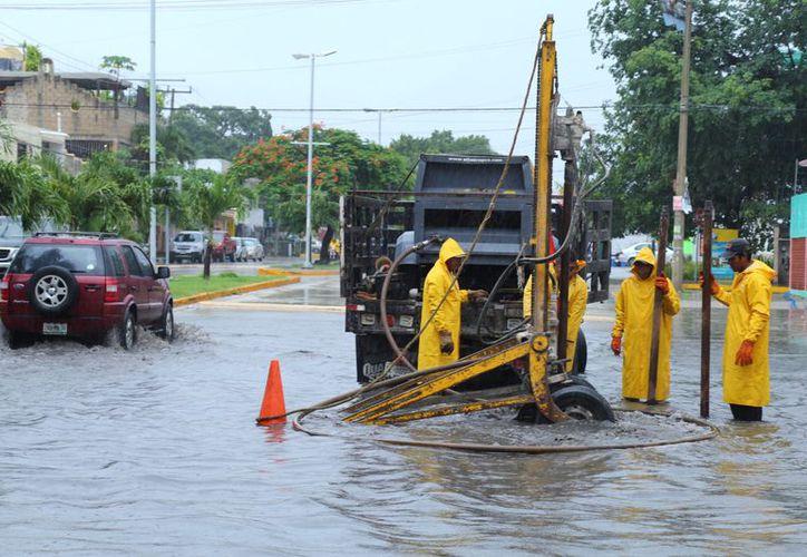 Realizan trabajos de desazolve en las calles inundadas de Solidaridad. (Foto: Redacción)