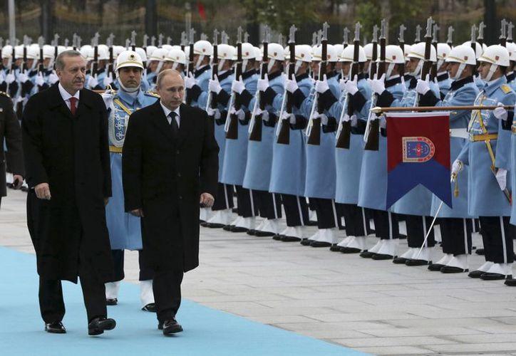 Rusia y Turquía mantienen buenos lazos comerciales, pero algunas diferencias en los conflictos de la región. En la imagen, Putin pasa revista a las tropas turcas junto al presidente Recep Tayyip Erdogan. (AP)