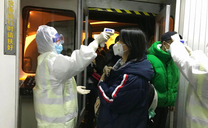 Funcionarios de salud revisan la temperatura corporal de los pasajeros que llegan de la ciudad de Wuhan al aeropuerto de Beijing, el miércoles 22 de enero de 2020. (AP Foto Emily Wang)