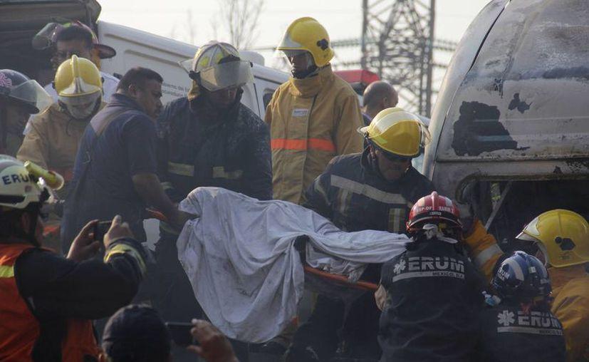 Rescatistas retiran un cadáver del sitio del accidente. Además de los muertos, resultaron afectados 45 domicilios y 16 vehículos dañados. (Agencias)