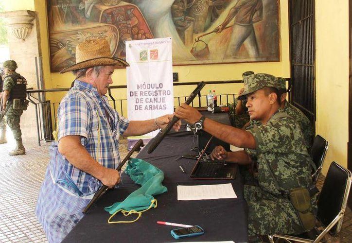 Un meridano canjea un arma en los bajos del Palacio Municipal, en el marco del programa Canje y Registro de Armas 2015. (SIPSE)