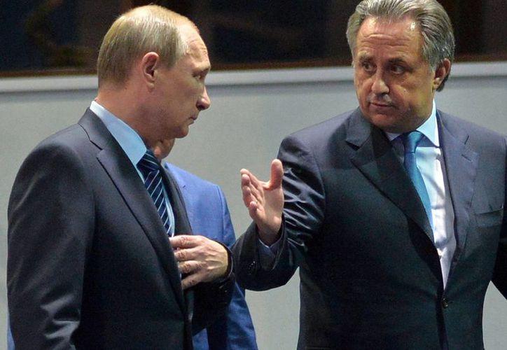 El presidente ruso, Vladimir Putin (izq) y el ministro de deportes, Vitaly Mutko, durante una reunión con los presidentes de las federaciones deportivas ante el escándalo masivo de dopajes que ataca en estos momentos al país euroasiático. (Archivo AP)