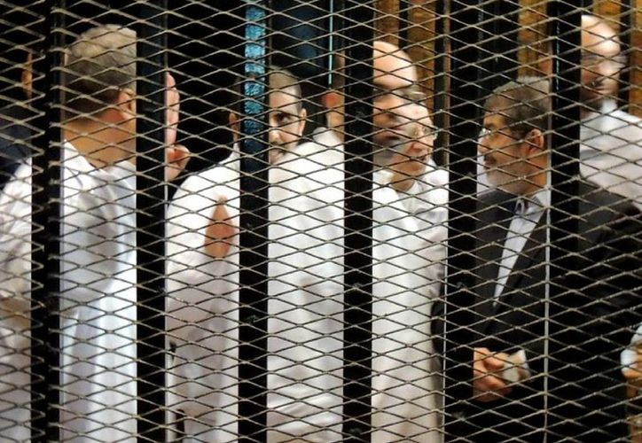 Mohamed Mursi (d), y otros acusados en la primera sesión del juicio contra él y otros 14 dirigentes islamistas, en El Cairo, Egipto. (Archivo/EFE)