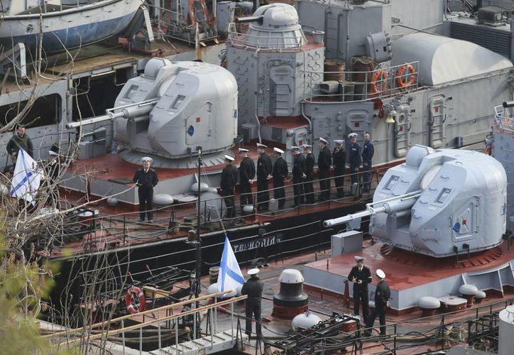 Marineros ucranianos, que han decidido permanecer en sus barcos y servir a Rusia, participan en la ceremonia de izado de bandera a bordo de los buques Ternopol (izq) y Khmelnitsky en el puerto de la bahía de Crimea, en Sebastopol (Ucrania), el miércoles 26 de marzo de 2014. (EFE)