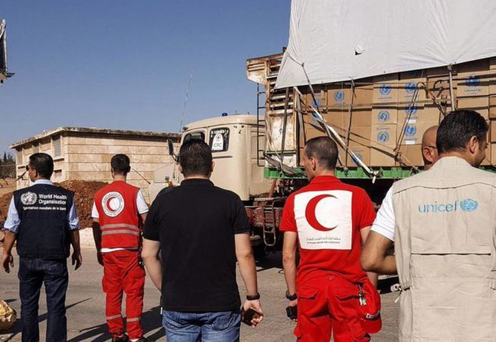 Fotografía cedida por la Media Luna Roja Siria, que muestra un convoy de camiones antes de partir para entregar ayuda humanitaria en el área rural de Alepo, Siria. (EFE)