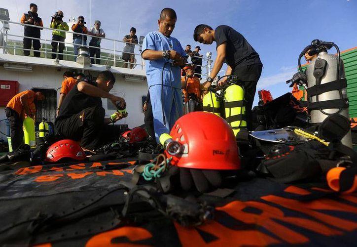 Rescatistas se preparan para lanzarse al mar, tras los hallazgo de varios cadáveres del vuelo de AirAsia que cayó la semana pasada. (AP)